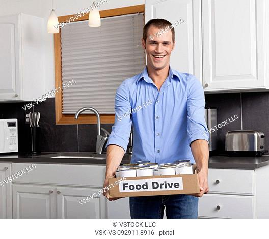 USA, Illinois, Metamora, Portrait of smiling man holding cardboard box with canned food in kitchen