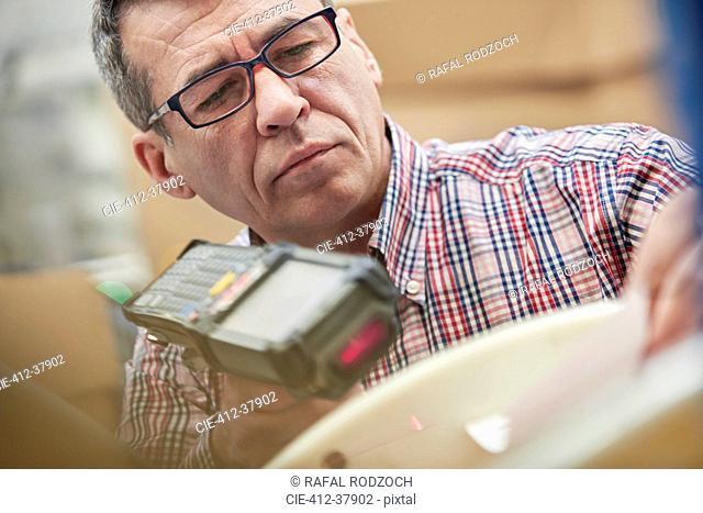 Focused male worker using IR code scanner in fiber optics warehouse
