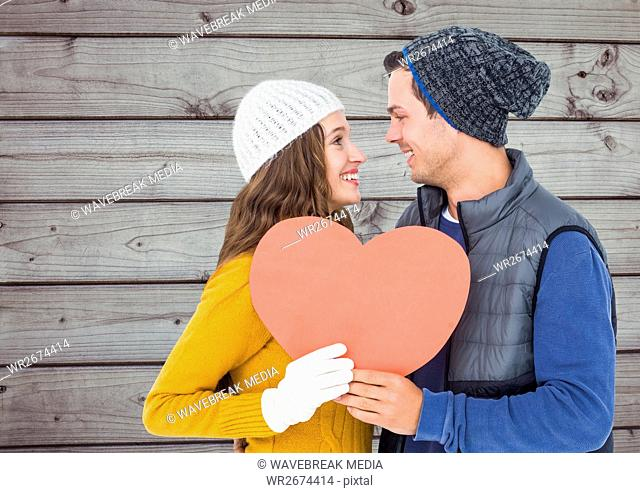 Couple standing face to face and holding heart together