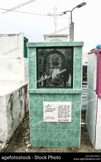 Enclosed memorial chamber with grave offerings, photograph, picture of Jesus and a wrought iron arched door with a cross atop a green tiled tomb in Champoton