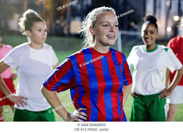 Confident young female soccer players resting with hands on hips on field at night