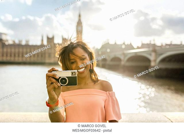 UK, London, beautiful woman taking a picture near Westminster Bridge