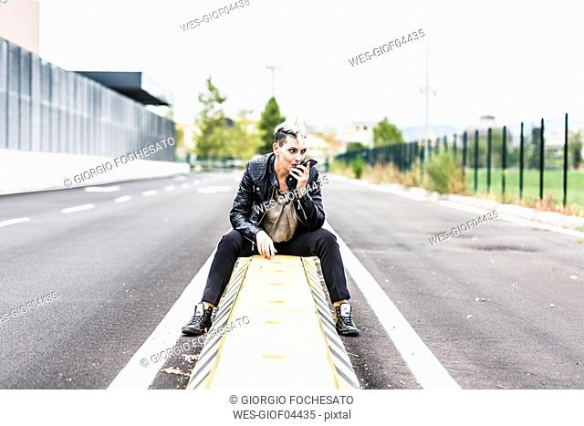 Punk woman sitting at the roadside using cell phone