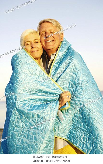 Close-up of a mature couple wrapped in a blanket and smiling