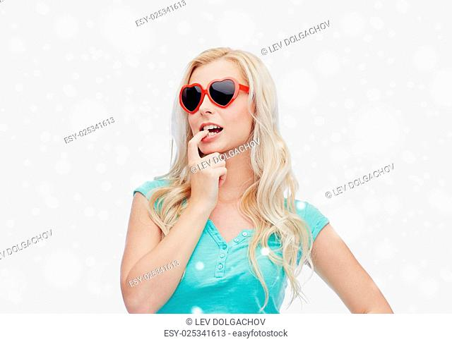 valentines day, winter holidays, christmas and people concept - smiling young woman or teenage girl in heart shaped sunglasses over snow