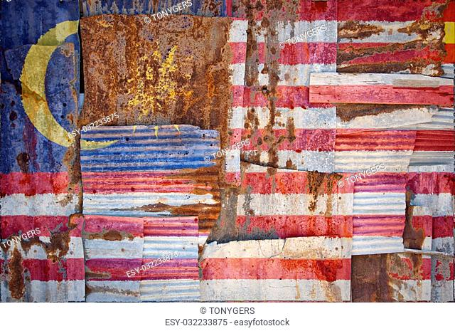 An abstract background image of the flag of Malaysia painted on to rusty corrugated iron sheets overlapping to form a wall or fence