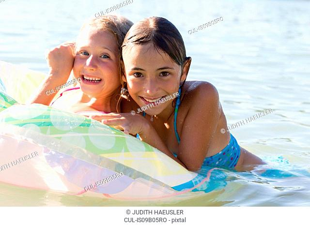 Portrait of two sisters playing with inflatable ring in Lake Seeoner See, Bavaria, Germany