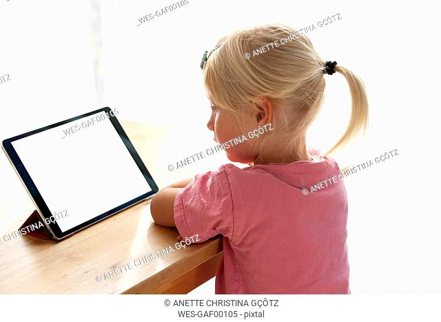 Profile of blond little girl using digital tablet at home
