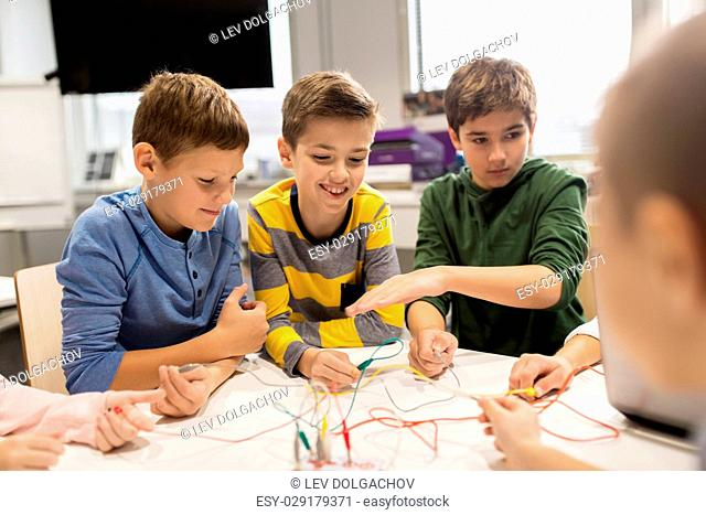 education, children, technology, science and people concept - group of happy kids with invention kit at robotics school lesson