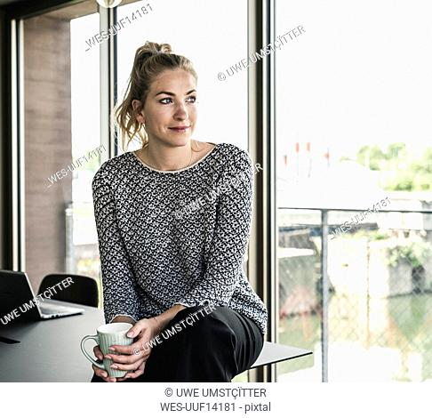 Young woman sitting in office, taking a break, drinking coffee