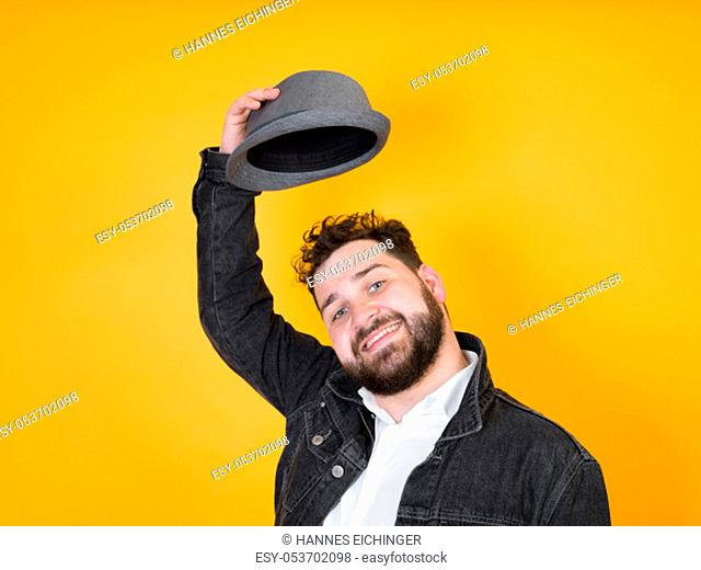 cool man with hat and black beard in front of yellow, orange background and is happy