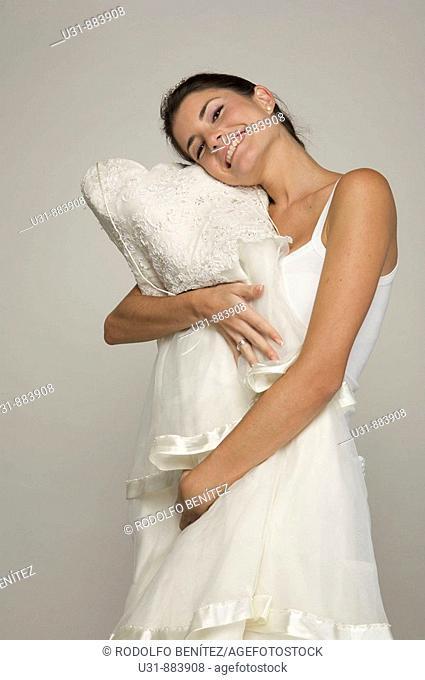Bride in her 20s hugs her wedding dress