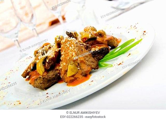 Meat under tasty sauce in plate
