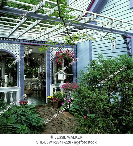 PORCHES: View towards porch from brick walkway, flowering plants in planter, white wood trellios work overhead