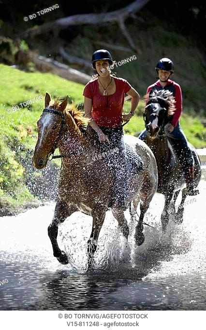 horseriders cantering through river