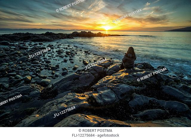 Woman sits on the shore of the Pacific Ocean watching the sunset near Jordan River; Vancouver Island, British Columbia, Canada