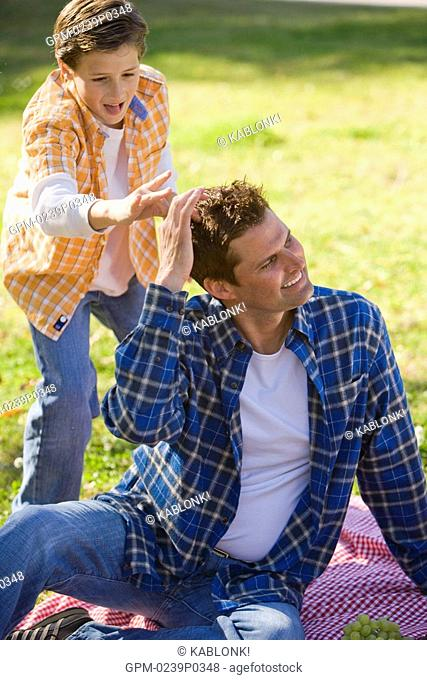 Happy father and son sitting in park, boy gesturing towards father