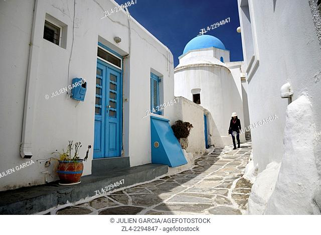 Woman walking in a narrow street in the village of Lefkes, small church with a blue dome. Greece, Greek islands in the Aegean sea, the Cyclades, Paros island