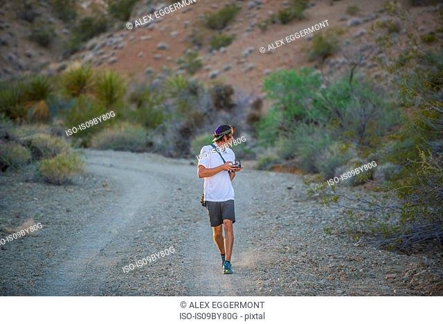 Man walking along dirt track operating drone (unmanned aerial vehicle)