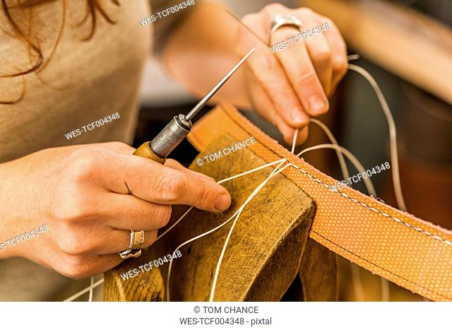 Woman sewing elastic fabric rubber band using lacing pony and awl