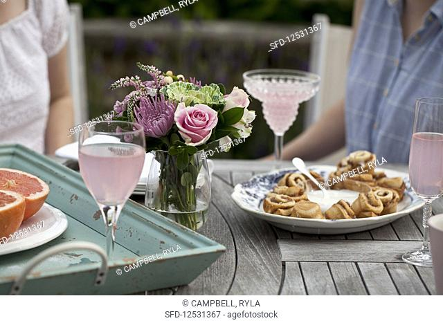 Two women sitting at an outdoor brunch table with flowers, grapefruit halves, glasses of sparkling strawberry lemonade, cinnamon buns and icing