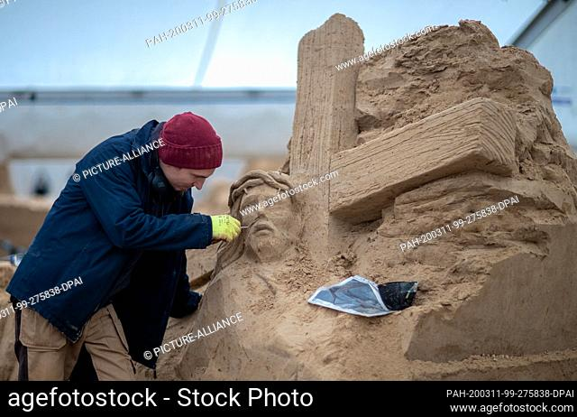 10 March 2020, Mecklenburg-Western Pomerania, Binz: A sand artist is working on a Christ figure at the sand sculpture festival. On 14.03