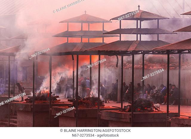 Funeral pyres are tended for many hours until cremated corpses are turned to ash, Pashupatinath Temple, a Hindu temple along the Bagmati River in Kathmandu