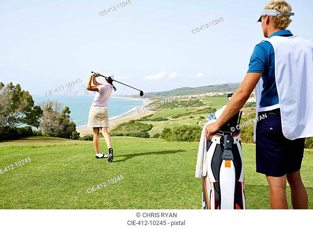 Caddy watching woman tee off on golf course overlooking ocean