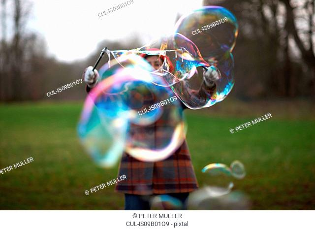 Woman in park using bubble wand to make bubbles