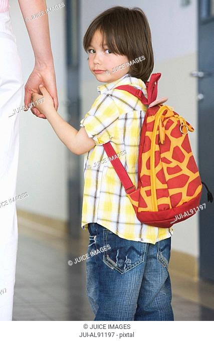 Preschool boy holding adultis hand