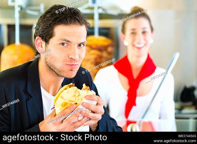 Doner kebab - friendly vendor and customer in a Turkish fast food eatery, with a freshly made pita bread or kebab in front of skewer