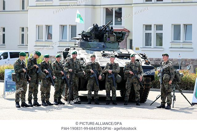 """27 August 2019, Saxony, Frankenberg: Soldiers of the Panzergrenadierbrigade 37 stand in front of an armoured infantry fighting vehicle """"""""Marder"""""""" in the Wettin..."""