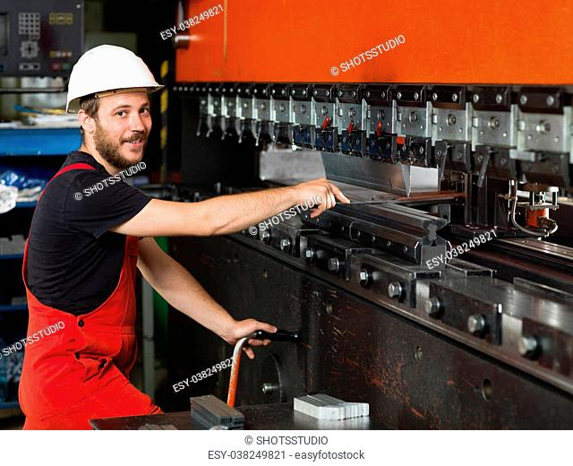 right side close-up of a worker, standing, looking happy, wearing red overalls, and a white protective helmet assisting an industrial machinery