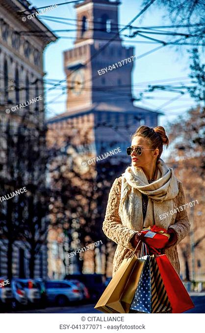 Rediscovering things everybody love in Milan. elegant tourist woman with shopping bags and Christmas gift near Sforza Castle in Milan, Italy looking aside