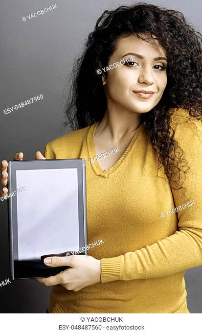 Going to work. Amazing girl with enigmatical smile wearing yellow cardigan holding black tablet in her hands while looking at camera