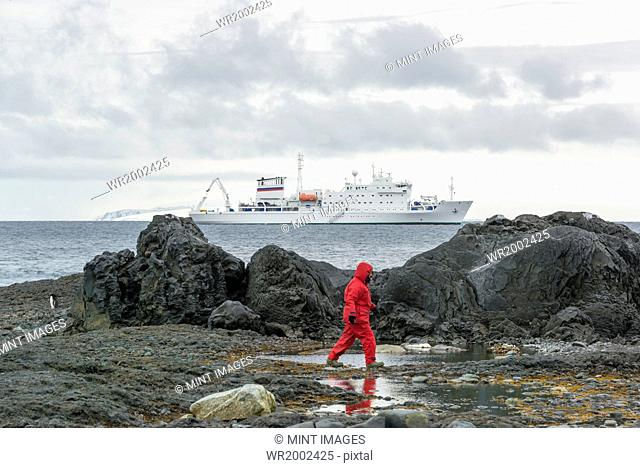 Man walking along rocks by the sea, a polar research vessel in the background on the ocean