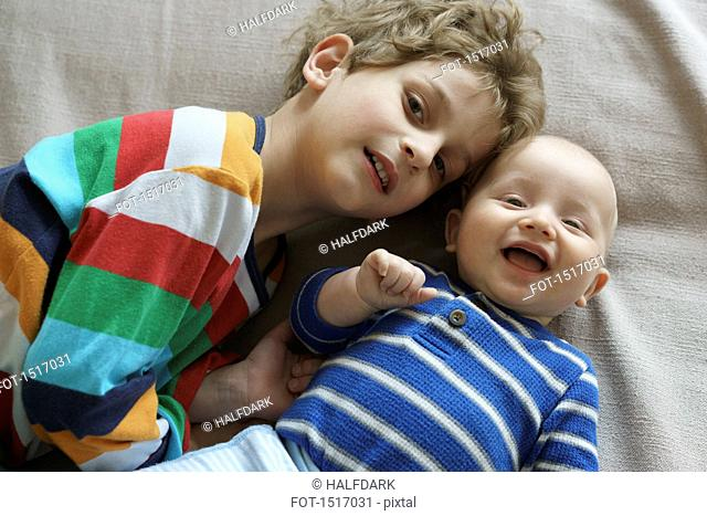 High angle portrait of brothers lying on bed at home