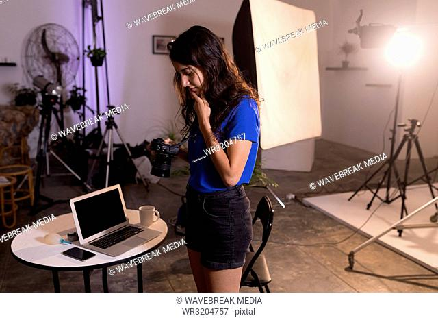 Female model looking at digital camera