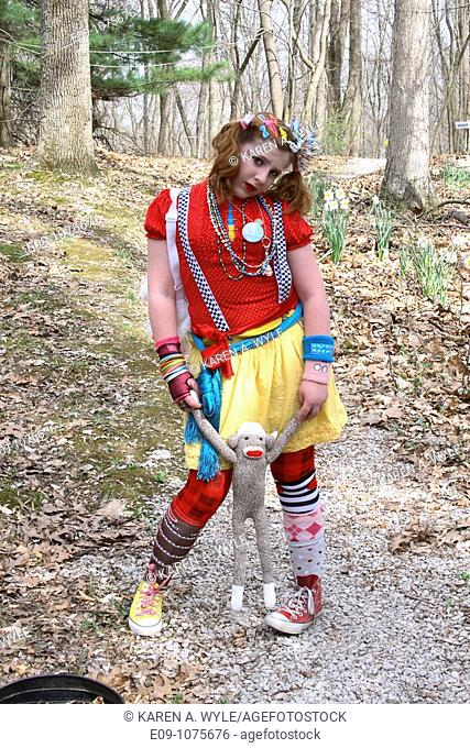 red-haired teenaged girl dressed in Colorful Decora style, holding a sock monkey, on path with trees and daffodils behind her