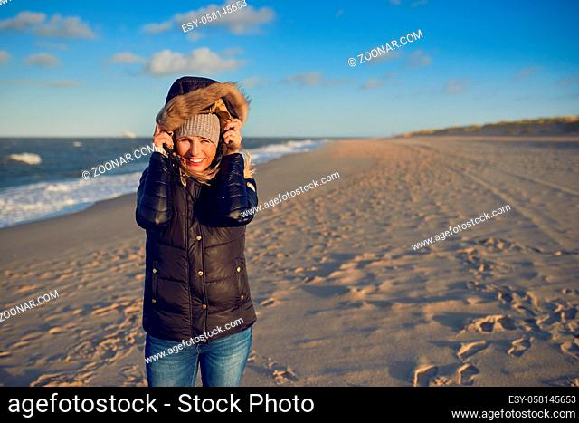 Portrait of a beautiful woman smiling while wearing a black waterproof hooded winter coat on an empty beach with an old lighthouse at the horizon