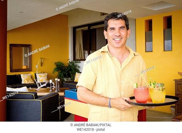 Smiling hispanic man, 50 years old, is serving cocktails on a tray