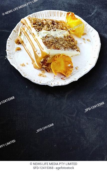 A slice of hummingbird cake with pineapple, bananas, grated coconut, pecan nuts, caramel sauce, cream cheese, cinnamon and whisky