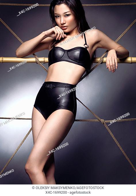 Edgy fashion photo of a beautiful sexy asian woman wearing a black trendy bikini swimsuit