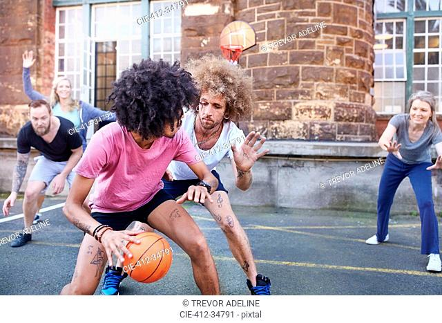 Friends playing basketball on urban basketball court