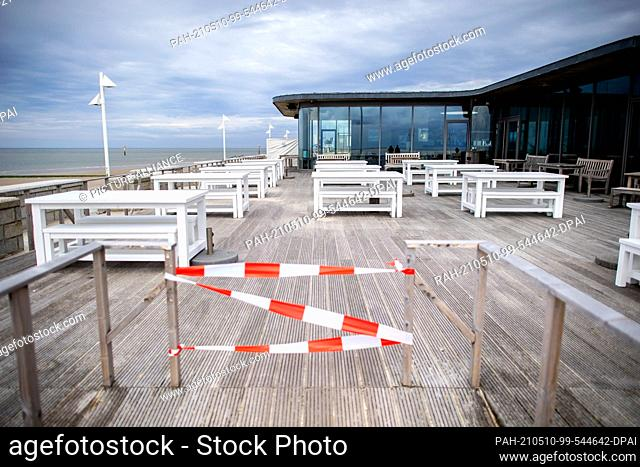 10 May 2021, Lower Saxony, Norderney: Numerous empty tables of the outdoor gastronomy stand on the still closed terrace of the Milchbar at the beach promenade