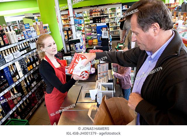 Cashier scanning goods and food with clients in a supermarket