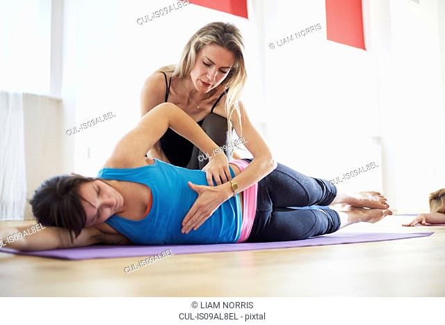 Young woman and tutor in pilates class