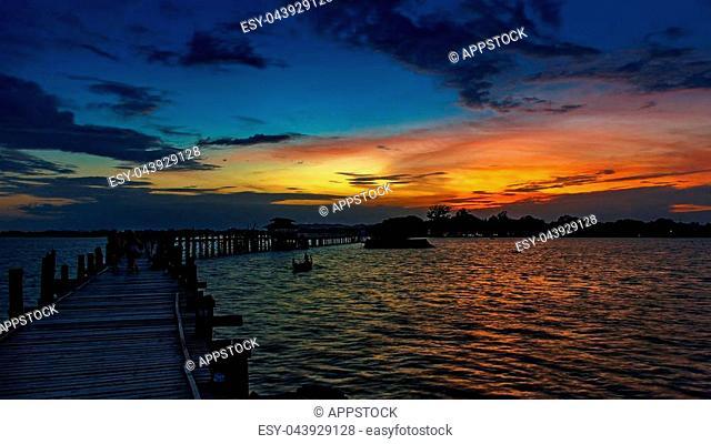 Sunset with silhouettes of people on Bridge U-Bein teak bridge is the longest. in Amarapura ,Mandalay ,Myanmar