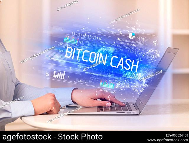 Closeup of businessman hands working on laptop with BITCOIN CASH inscription, succesfull business concept