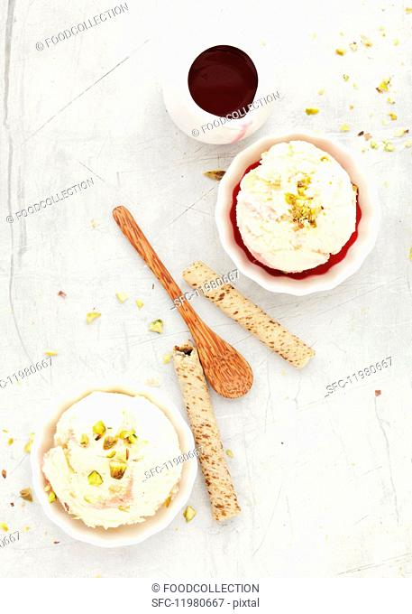Scoops of ice cream served with pistachio nuts, red fruit coulis and wafer rolls